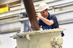 Operator installs a transformer in an industrial plant in mechanical engineering royalty free stock images