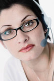 Operator is listening. Beautiful young woman with charming big green eyes is bearing modern glasses and receiving calls on a headset royalty free stock images