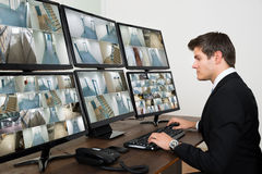 Operator Looking At Multiple Camera Footage. Young Male Operator Looking At Multiple Camera Footage On Computers Royalty Free Stock Image