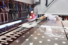 Operator of machine sets workpiece into automatic panel flexor. Operator of the machine sets the workpiece into an automatic panel flexor Stock Images