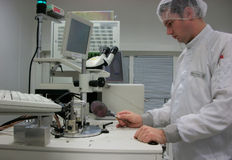 Operator of the measuring station with the silicon. The operator of the measuring station with the silicon wafer Stock Photography