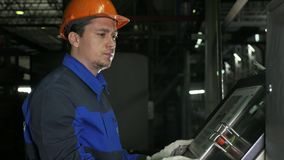 Operator monitors control panel of production line. Manufacture of plastic water pipes factory. Process of making. Operator monitors control panel of production stock photography