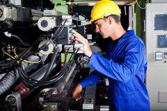 Operator operating machine. Male caucasian machine operator operating industrial printing machine Stock Photography