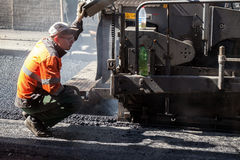 Operator of paver machine works on a control pane. Saint-Petersburg, Russia - May 30, 2015: men at work, urban road under construction, operator of paver machine Royalty Free Stock Photography