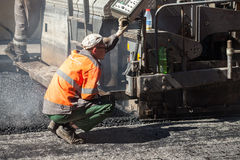 Operator of paver works on a control panel. Saint-Petersburg, Russia - May 30, 2015: men at work, urban road is under construction, operator of paver machine Royalty Free Stock Photography