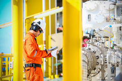 Operator recording operation of oil and gas process at oil and rig plant, offshore oil and gas industry, offshore oil and rig. In the sea, operator monitor Royalty Free Stock Image