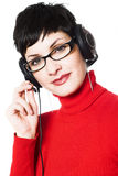Operator in red. Beautiful young woman with charming big green eyes is bearing modern glasses and receiving calls on a headset Royalty Free Stock Images