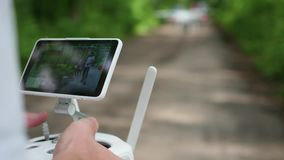 The operator remotely controls the drone. The flight of the drone stock footage