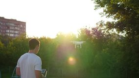 The operator remotely controls the drone. The flight of the drone stock video footage