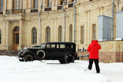 The operator removes the historical film using quadrocopters on the background of old cars and Gatchina Palace Royalty Free Stock Photography