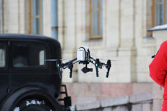 The operator removes the historical film using quadrocopters on the background of old cars and Gatchina Palace Royalty Free Stock Photo
