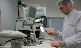 The operator with the silicon wafer. The operator of the measuring station with the silicon wafer Stock Image