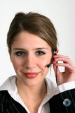 Operator standing by. Pretty young woman in business attire with a telephone headset Stock Images