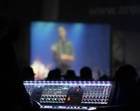 Operator table sound at the concert. The sound operator`s table, the audience background, and the scene with the single artist performing Royalty Free Stock Image