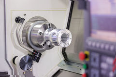 Operator turning aluminium autopart by cnc lathe. In industrial factory stock photo