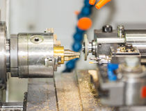 Operator turning and grinding brass autopart by cnc lathe Stock Photography