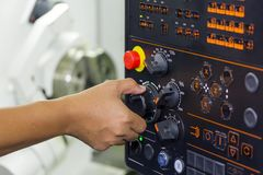 Operator use hand turns dial switch control at panel for adjust parameter of cnc lathe machine at factory.  royalty free stock photo
