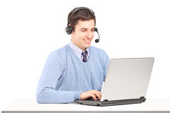 Operator wearing headset and working on a laptop Stock Image