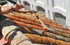 Operator who manages the pressurized water jet to clean the lichen in the shingles on the roof of a house. Construction workman doing cleaning the shingles with Royalty Free Stock Image