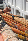 Operator who manages the pressurized water jet to clean the lichen in the shingles on the roof of a house. Construction workman doing cleaning the shingles with Stock Photo