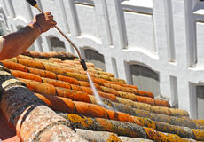 Operator who manages the pressurized water jet to clean the lichen in the shingles on the roof of a house. Construction workman doing cleaning the shingles with Stock Photos