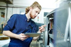 Operator at work. Young operator examining printing machine on factory royalty free stock image