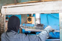 Operator or worker use steel plate for inspection product after press down by manual hydraulic bending machine at factory.  stock photography