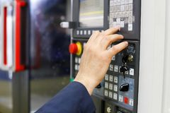 Operator working with CNC machining center. Using control panel. Selective focus Stock Photography
