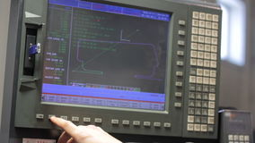 Operator working with control panel of CNC machining centerchanging numbers stock video footage