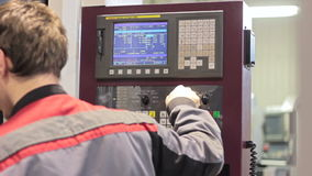 Operator working with control panel of CNC machining centerchanging numbers stock video