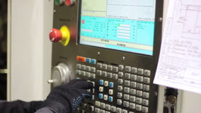 Operator working with control panel of CNC machining centerchanging numbers stock footage