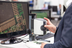 Operator working on digital microscope, inspecting electronic component Stock Images