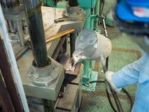 Operatore che versa fuso di alluminio dentro all'alta precisione che fonde Mo Immagine Stock
