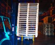 Operatore del carrello elevatore che tratta i pallet di legno in carico del magazzino per trasporto alla fabbrica del cliente fotografia stock libera da diritti