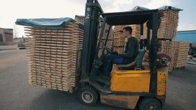 Operatore del carrello elevatore che tratta i pallet di legno in magazzino Uomo facendo uso del pacchetto di dor del caricatore d video d archivio