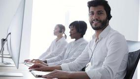 Operatore della call center Uomo nel funzionamento della cuffia avricolare al centro del contatto archivi video