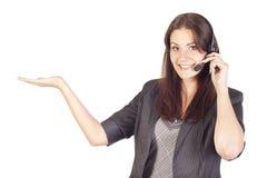 Operatore della donna con la cuffia avricolare che presenta il vostro produc Immagini Stock