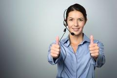 Operatore di call center attraente che dà i pollici su Immagini Stock Libere da Diritti