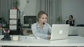 Operatore di call center sorridente che lavora con il computer portatile facendo uso della cuffia avricolare in ufficio stock footage