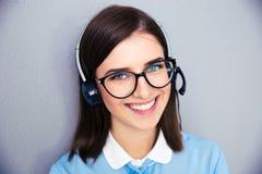 Operatore femminile sorridente con la cuffia avricolare del telefono fotografia stock