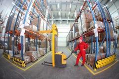 Operatore manuale del carrello elevatore sul lavoro in magazzino Fotografia Stock
