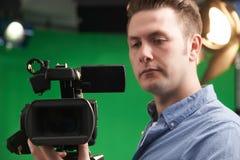 Operatore maschio della macchina fotografica nello studio della televisione immagini stock