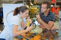 Operatore subacqueo femminile che ottiene consiglio circa i boccagli di immersione subacquea nel negozio di immersione subacquea immagine stock