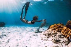 Operatore subacqueo libero della donna con le alette vicino a corallo sopra il mare sabbioso ed il serpente di mare fotografia stock