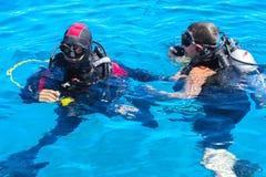 Operatori subacquei Mar Rosso del turchese e sul chiaro sull'immersione nei bei coralli ed in pesce variopinto immagini stock