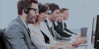 Operators with headsets in front of computers in the call center stock photo