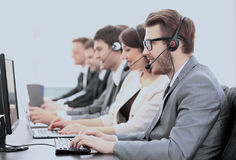 Operators with headsets in front of computers in the call center. Side view:call center operators in the headphones with microphones sitting in front of computer Royalty Free Stock Image