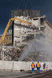 Operators oversee the demolition. Demolition of redundant building below dark blue sky Royalty Free Stock Image