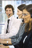 Operators taliking on headset. Young customer service representatives sitting in a row and talking on headset, smiling. Selective focus is placed on man Royalty Free Stock Images