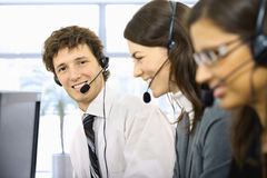 Operators taliking on headset. Young customer service representatives sitting in a row and talking on headset, smiling. Selective focus is placed on man Royalty Free Stock Photos